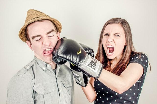 Žena s boxerskými rukavicami, ktorá udiera muža do tváre