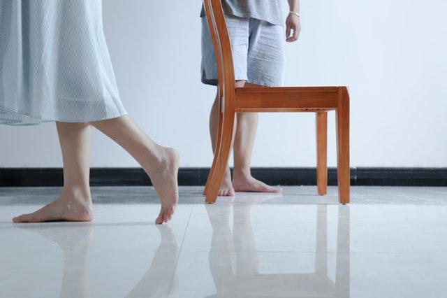 Dve osoby s bosými nohami v bielej miestnosti so stoličkou