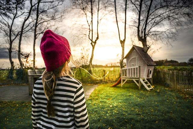 Dievčatko v čiapke sa pozerá na malý domček.jpg