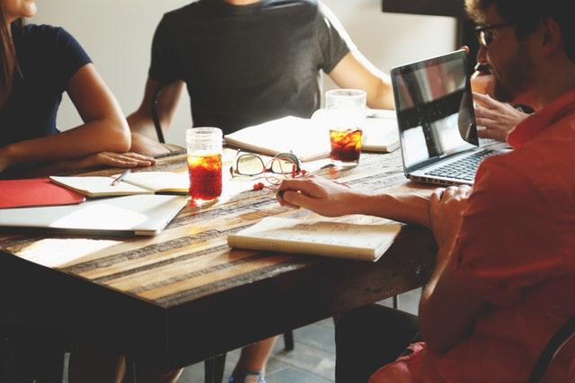 Skupina mladých ľudí sedí pri stole a pracujú.jpg