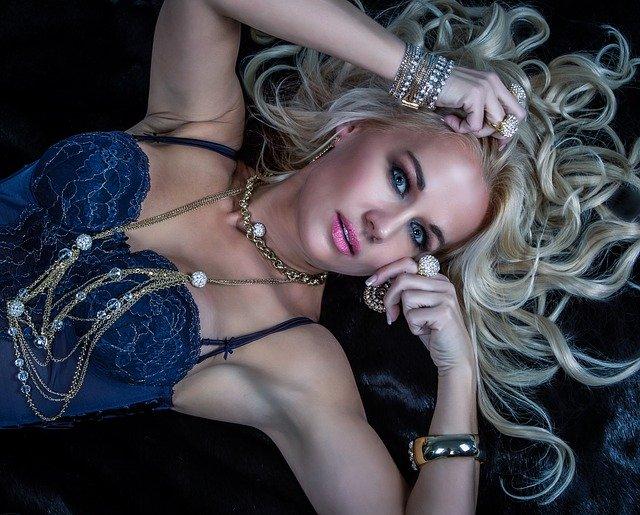 Žena v modrých šatách, s blond vlasmi, obvešaná šperkami.jpg