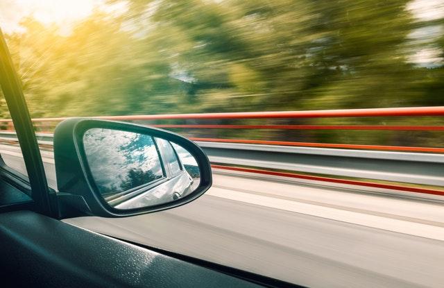 Spätné zrkadlo auta idúceho po ceste vedľa červeného zábradlia.jpg
