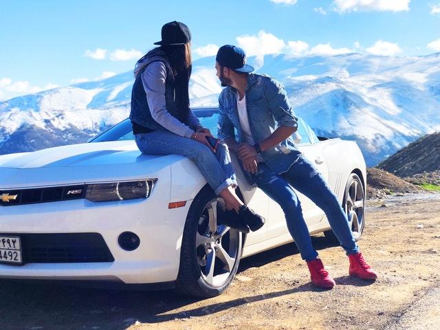 Muž a žena sú opretí o kapotu bieleho auta.jpg
