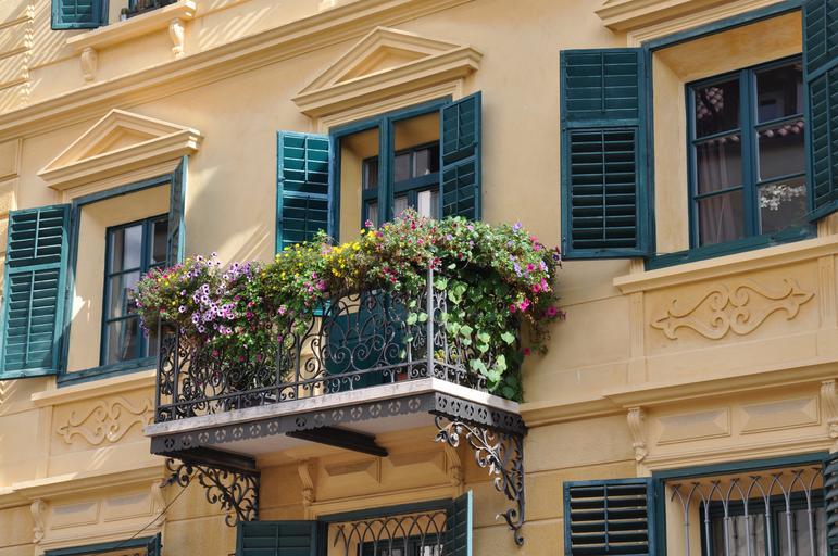 Balkón s kovovým zábradlím a množstvom kvetov.jpg